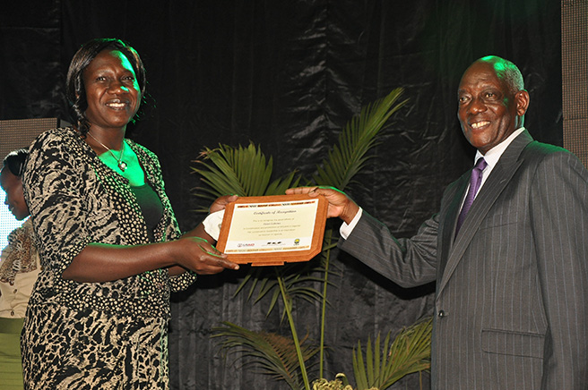 Helen Lubowa Executive Director of UCOTA receiving a certificate of recognition for Women in Conservation Leadership from UWA Board of Trustees Chairman