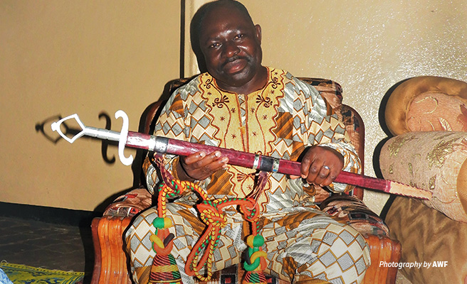 Photo of AWF Cameroon Country Coordinator holding ceremonial sword on receiving warrior title in Tchamaba chiefdom