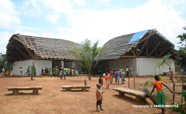 Photo of Ilima Conservation Primary School with untiled roof with children from the community in the foreground