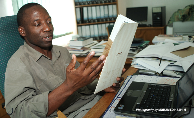 Photo of Dr Jimmiel Mandima sitting at his desk at African Wildlife Foundation DC office