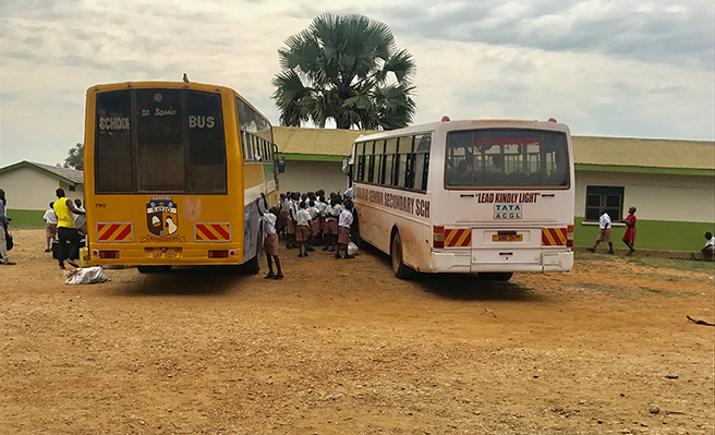 Photograph of children boarding buses for a field trip in Uganda Murchison Falls