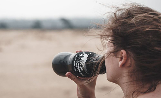 Photo of woman drinking from an African Wildlife Foundation Water to Go water bottle