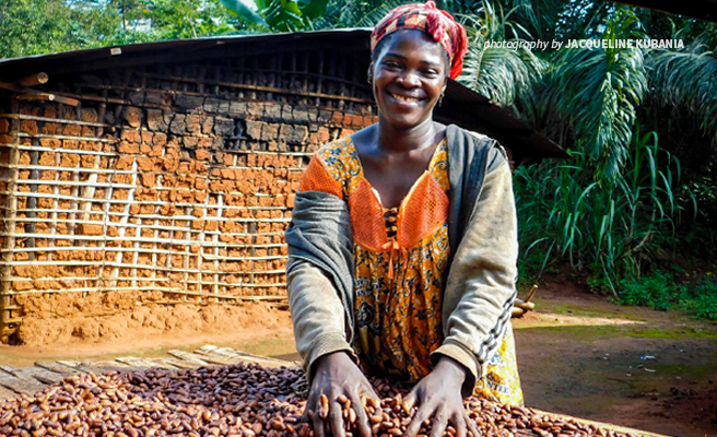 Photograph of woman cocoa farmer smiling and digging into her sustainable cocoa bean crop