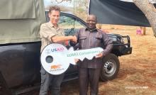 Photo of AWF CEO Tom Ogilvie-Graham presenting patrol vehicle to LUMO Conservancy Chairman John Ilume